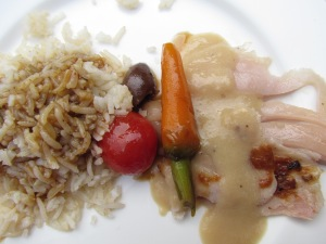 Rice with an excellent sauce, baby carrots & roasted pig topped with a sauce