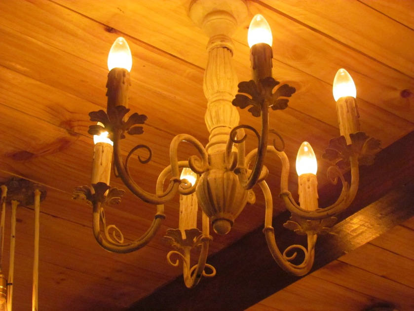 the chandelier hanging from wooden ceiling