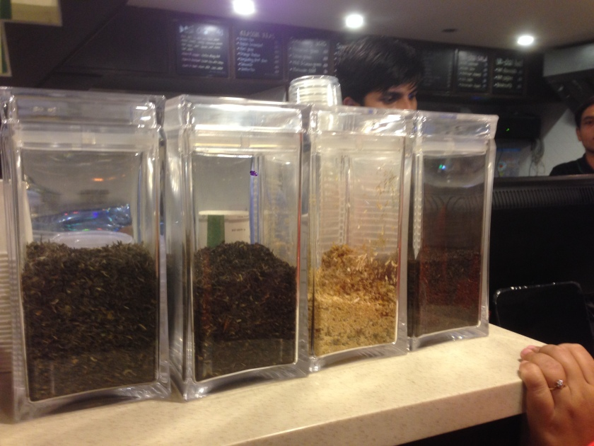 Different kind of tea leaves in transparent vessels , menu card on the wall in the backdrop