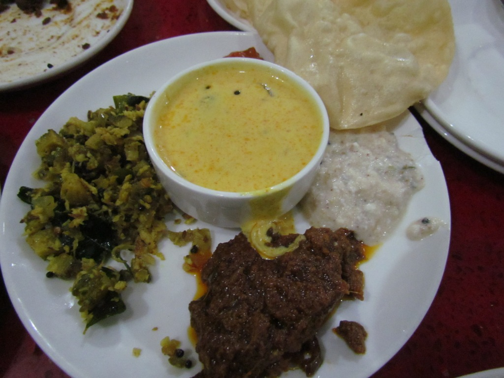 Kadhi in the center, red achaar on the side, karela dry curry & pachidi (off white).