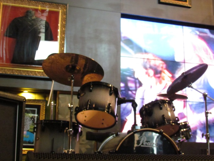 Drums on the stage in front of huge screen