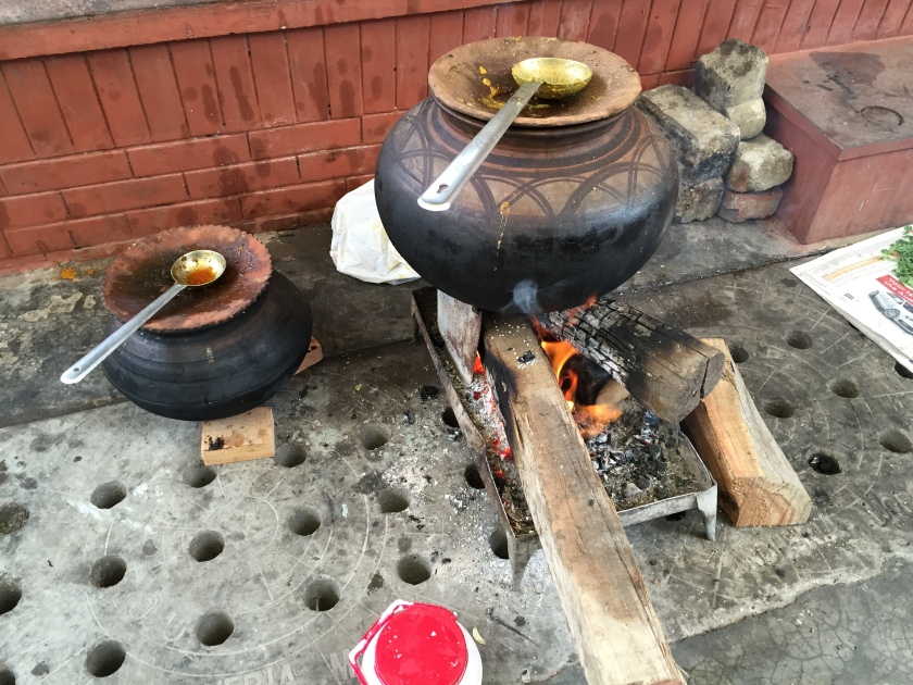 mutton being cooked on wood fire, inside earthen pot