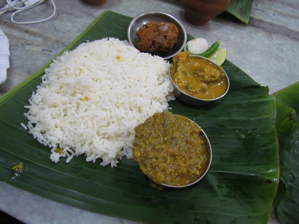 Food served on banana leaf placed on top of a stainless steel plate