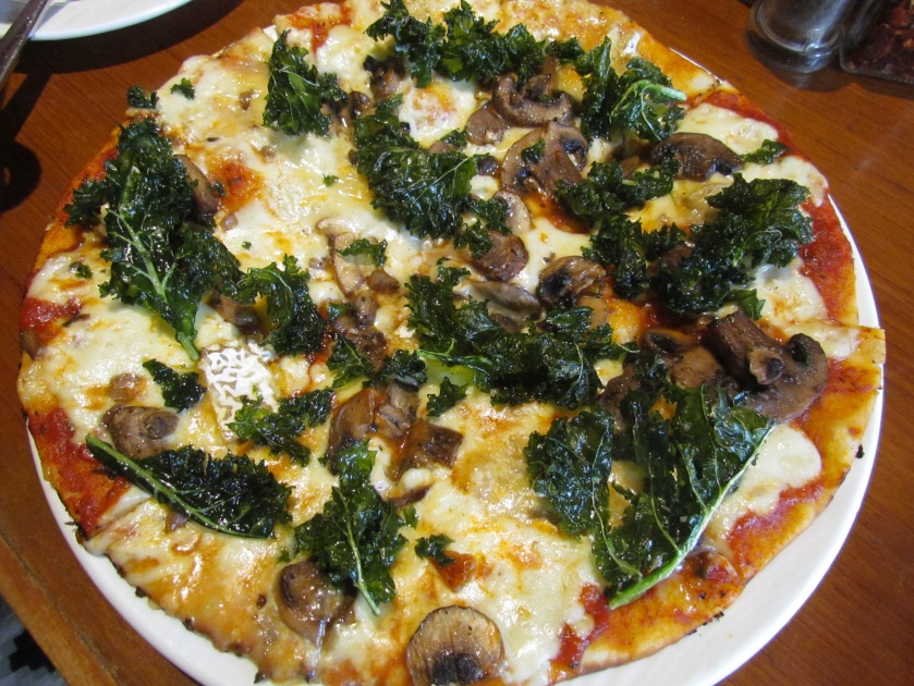 Spotted cow Camembert cheese with kale leaves on a thin crust pizza